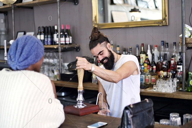 Man pouring draft beer for woman in bar