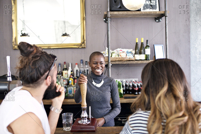 Smiling woman pouring beer for bar customers