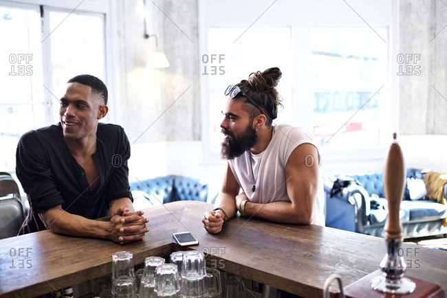 Two hip men at corner of a bar