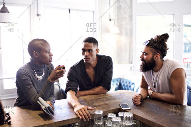 Three hip friends at the corner of a bar