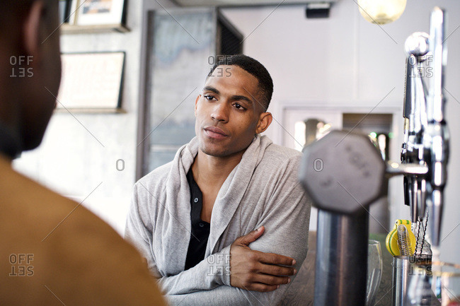 Man at a bar listening to a friend