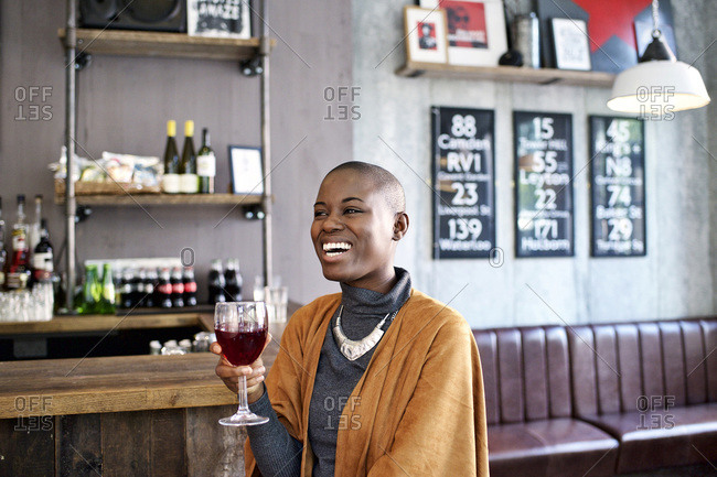 Woman laughing holding wine glass in bar