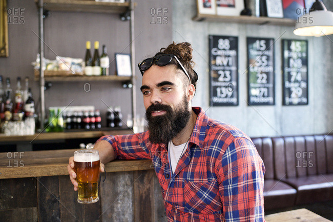 Man sitting at corner of bar with beer
