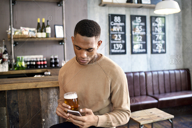 Man texting holding beer at corner of bar