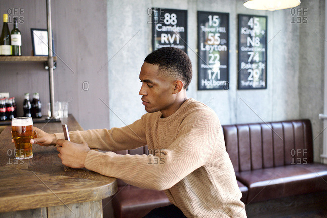 Man with phone holding beer at corner of bar