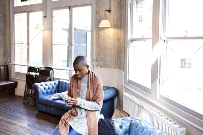 Woman on bar couch looking at phone