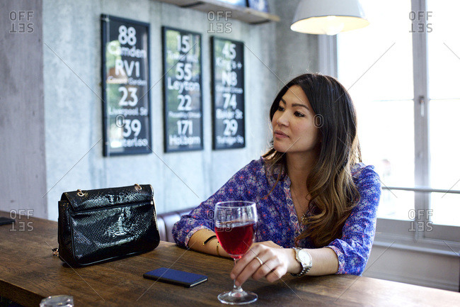 Woman in thought sitting at bar with wine