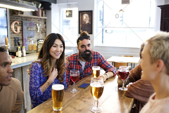 Five people chatting at a bar table