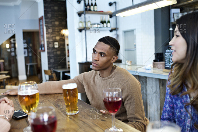 Man listening as friends chat at a bar