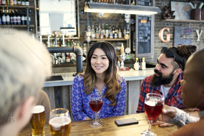 Woman listening as friends chat at a bar