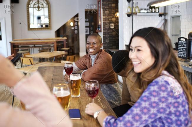 Friends laughing over drinks at bar table