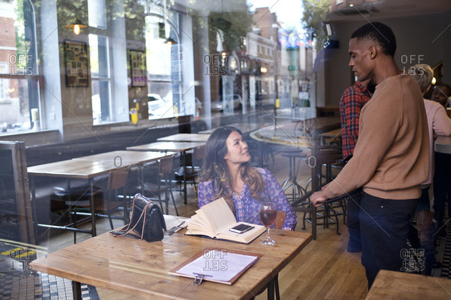 Server chatting to woman at bar with book and phone