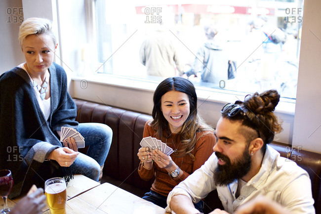 Friends playing a card game in a bar