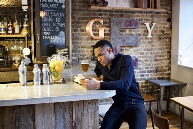 Man with phone, book, and beer at bar