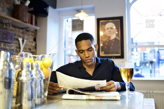 Man at corner of bar reading newspaper