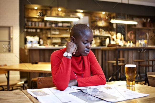 Woman reading a newspaper at a bar