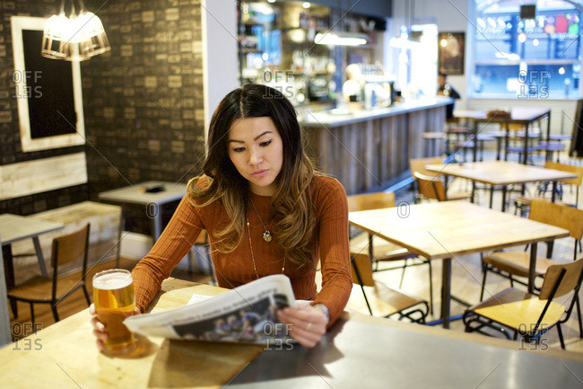 Woman reading a newspaper over a beer