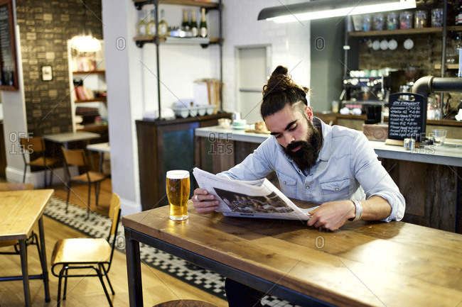 Stylish man reading newspaper in a bar
