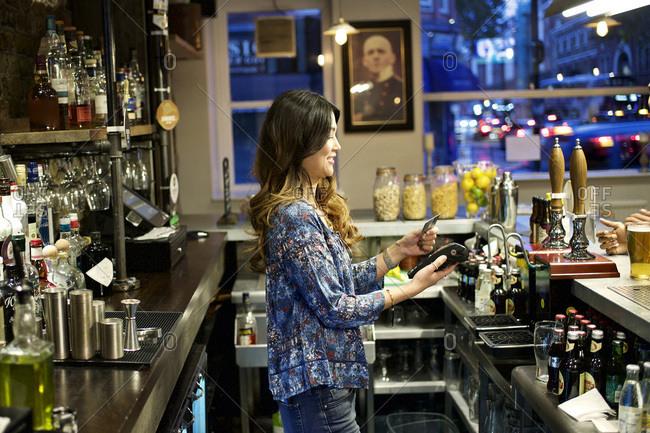 Female bartender with a credit card reader
