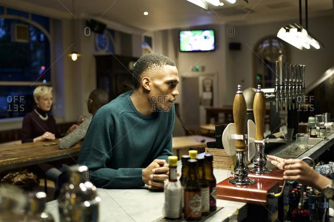 Man talking to a bartender at the bar