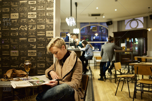 Woman reading newspaper in solitude at bar