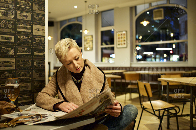 Woman reading newspaper in solitude at a bar