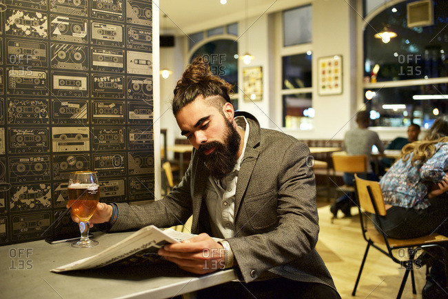 Man reading newspaper in solitude at a bar