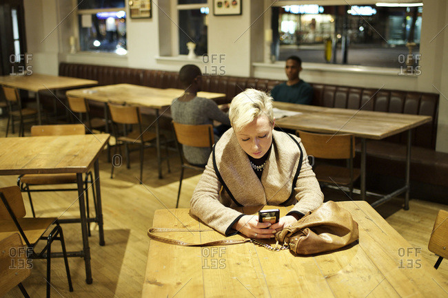 Woman alone at bar table checking her phone