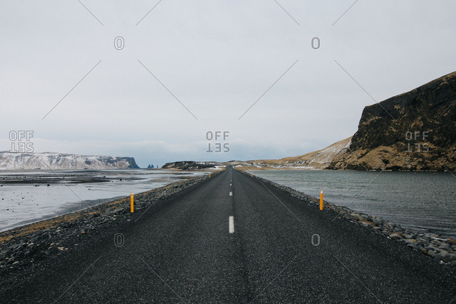 Road in Iceland passes between two lagoons with Reynisdrangar in the distance