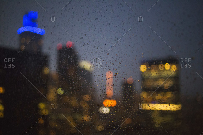Night time city view through a rainy window