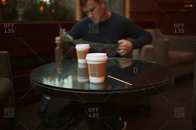 Close up of to-go coffees sitting on a table while man looks at a map
