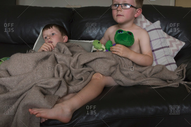 Two boys cuddling on a couch with a blanket