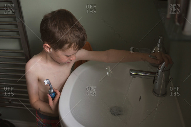 Little boy rinsing sink after brushing his teeth