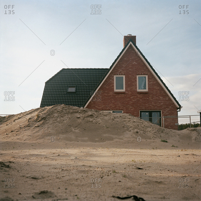 A newly built house behind a pile of sand