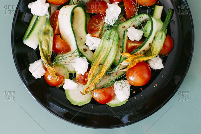 Salad with zucchini blossoms, tomatoes, and cheese