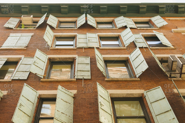 View of open shutters  and windows on brick building from below, New York City