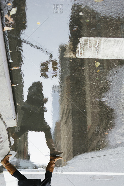 Woman crossing street reflected in puddle, New York City