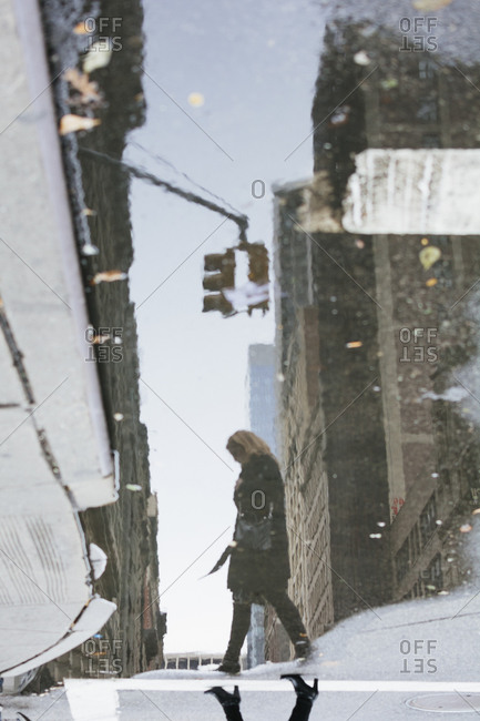 Woman crossing city street reflected in puddle, New York City