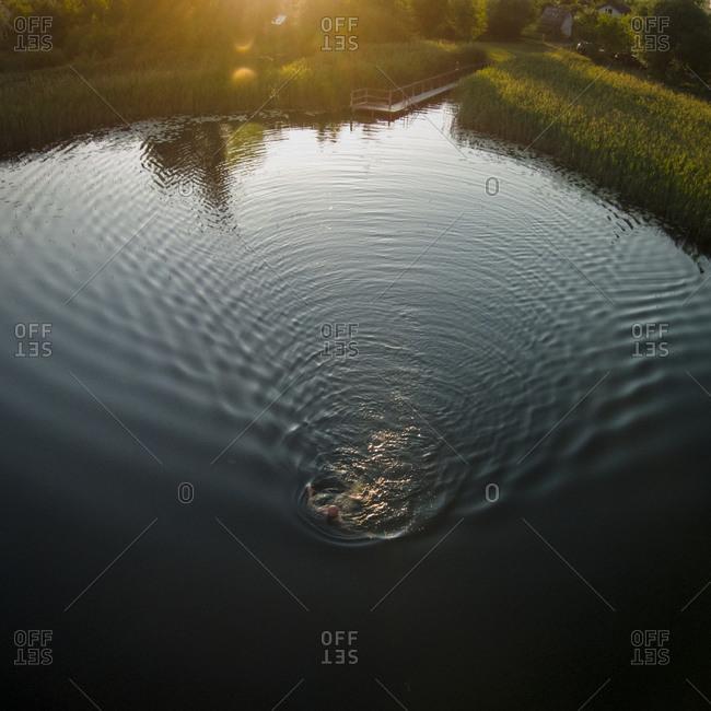 Man swimming in a lake at sunset in Elektrenai, Lithuania
