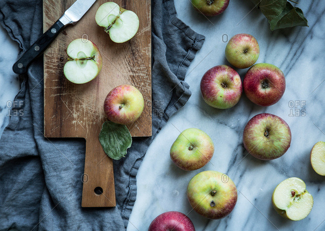 Fresh halved apples on a cutting board on a marble counter