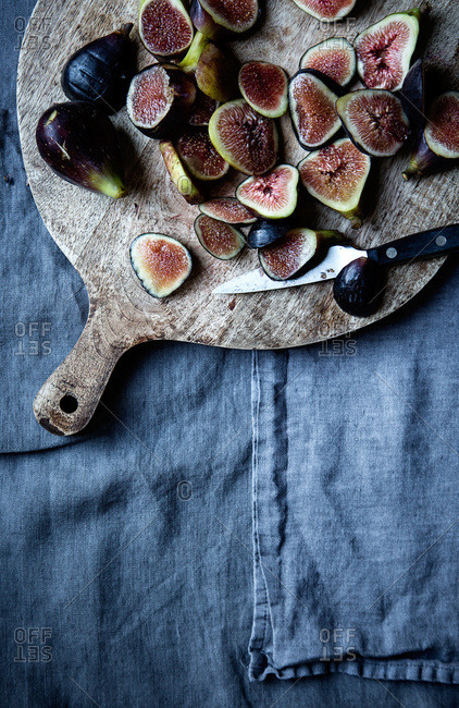 Black mission figs on a round wooden cutting board