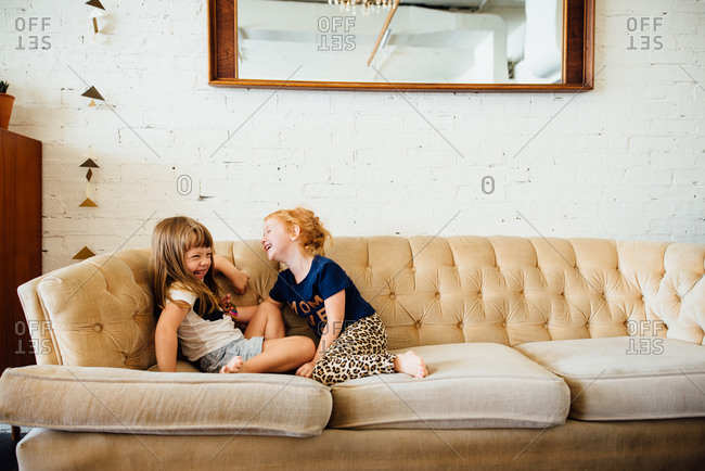 Two giggling young girls playing on couch