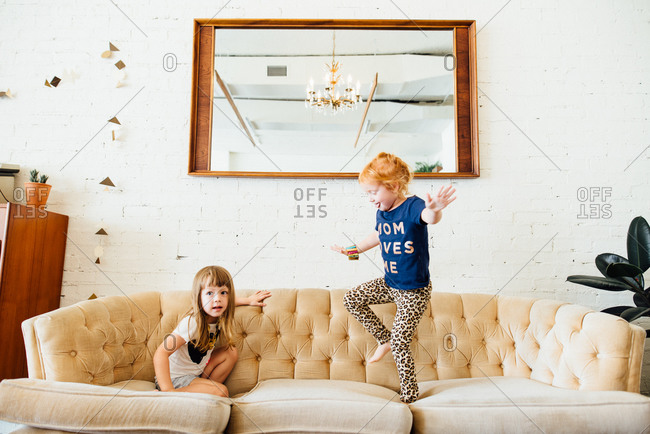 Two young children playing on sofa in living room