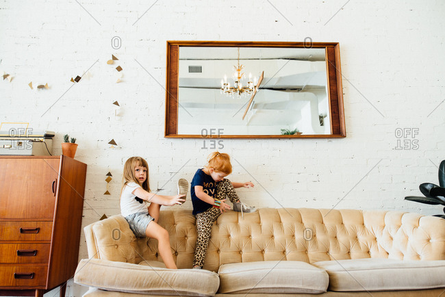 Two young girls climbing on sofa