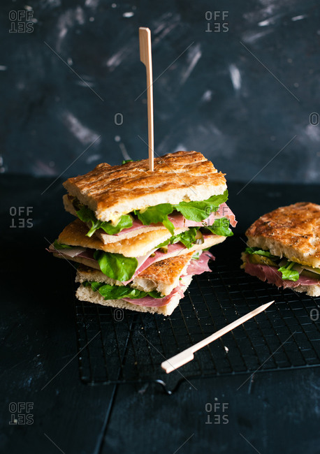 Stack of focaccia sandwiches on metal rack