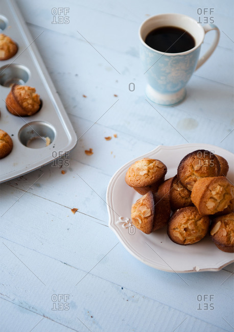Almond financiers with black coffee on white wooden table