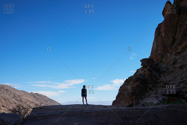 Back view of woman overlooking mountains from a rocky cliff