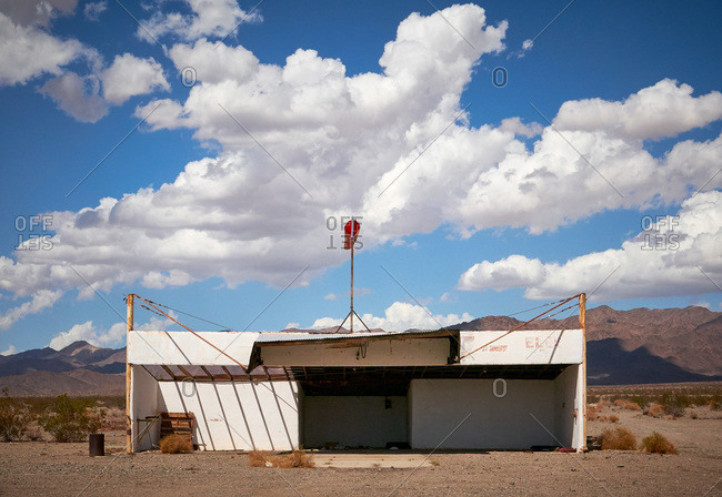 Abandoned building in desert with windsock on its roof