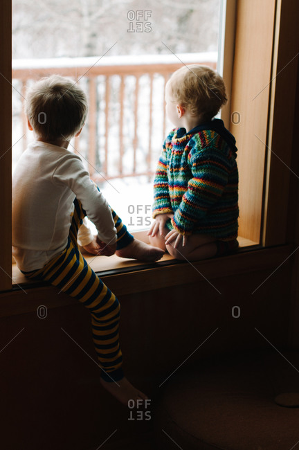 Two young brothers watch the snow fall outside the window