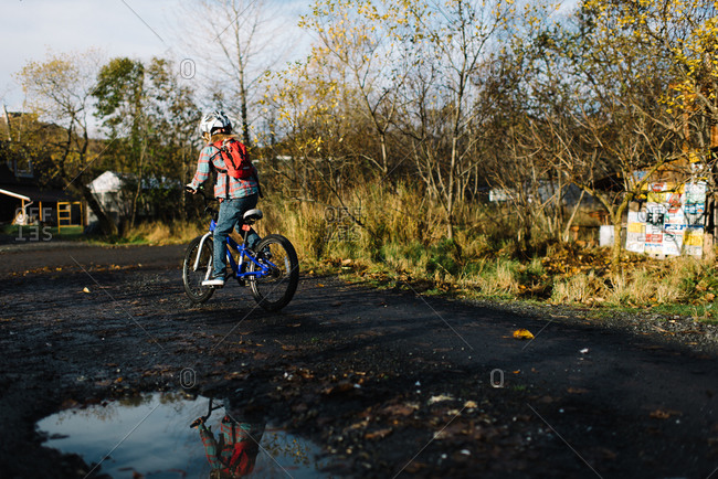 Child riding bike on dirt road in autumn